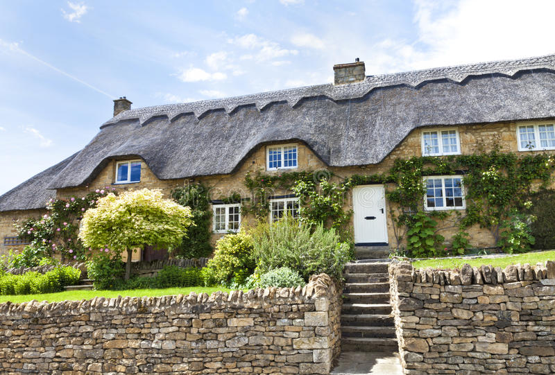 Download Stone Thatched Cottage With Flowers Wall Stock Image