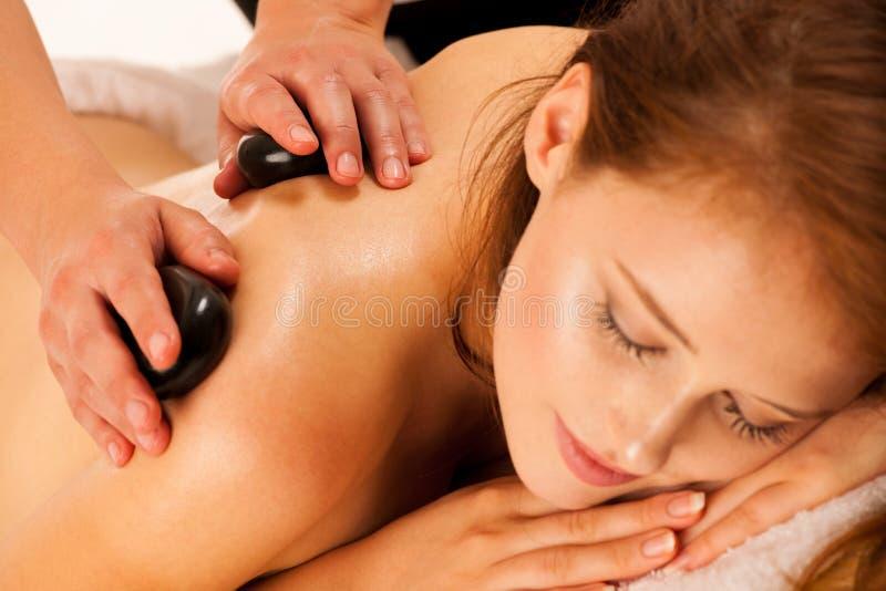 Stone therapy. Woman getting a hot stone massage at spa salon stock image