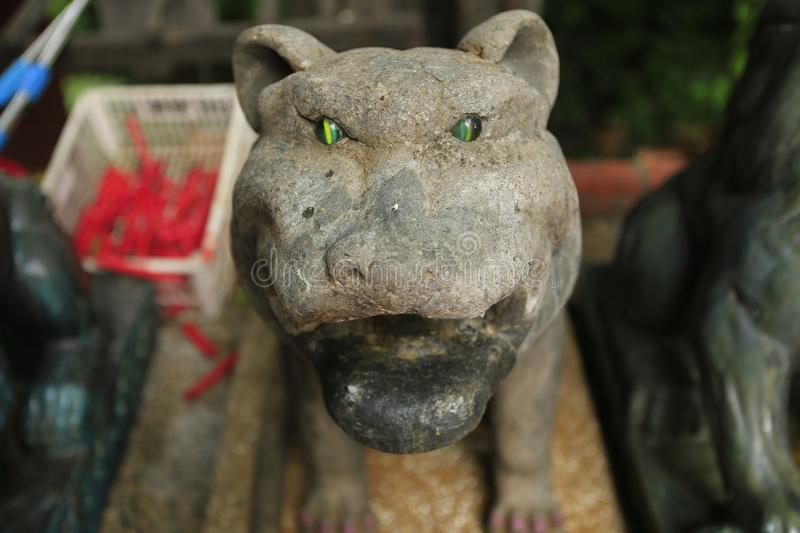 Stone tiger with emerald eyes. At the temple of Wat Phnom in Phnom Penh in Cambodia royalty free stock photos