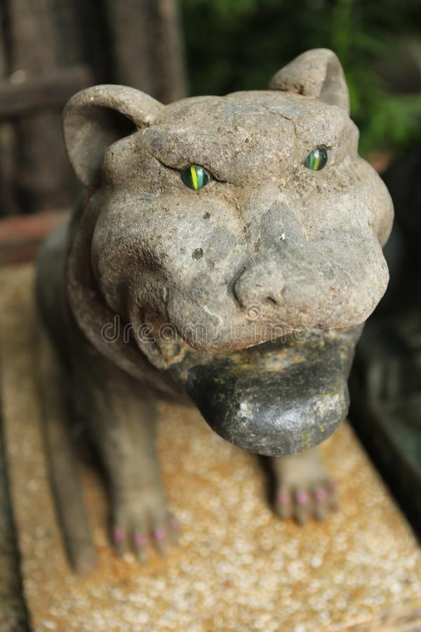 Stone tiger with emerald eyes. At the temple of Wat Phnom in Phnom Penh in Cambodia stock photography