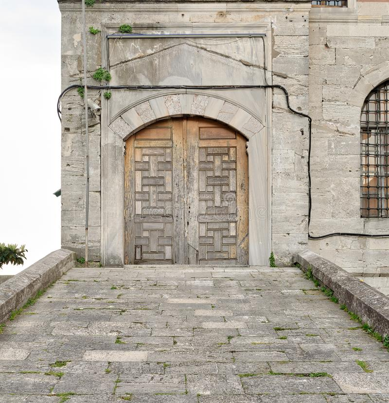 Stone tiled ramp leading to a wooden aged door over a stone wall royalty free stock image