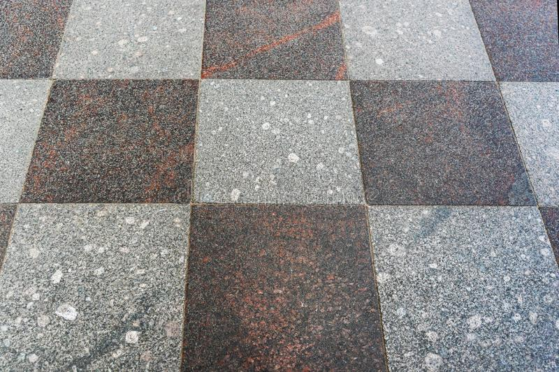 Stone tiles of gray tones, laid out in a checkerboard pattern. stock image