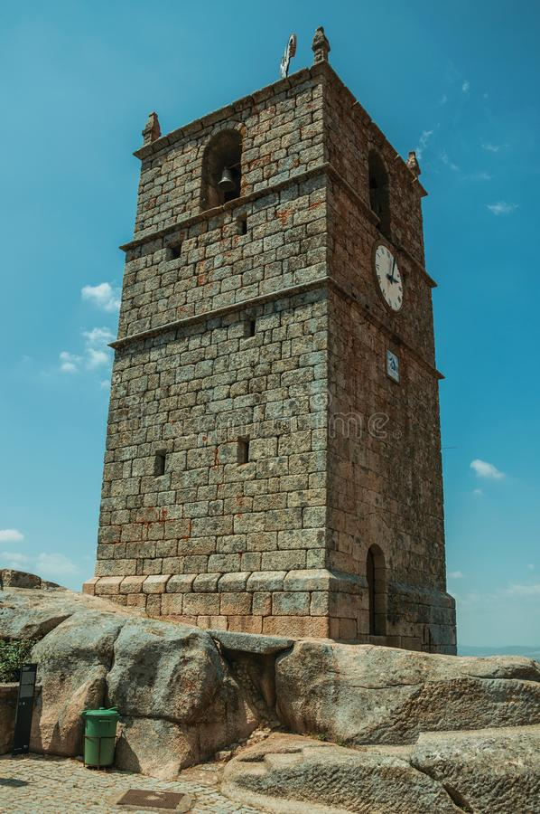 Stone tower with bell and clock in Monsanto. Charming facade of old stone tower with bell and clock over rocky hilltop in a sunny day at Monsanto. Considered one stock image