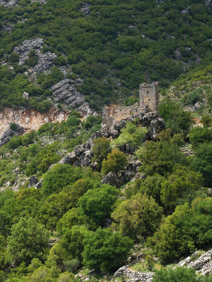 Stone tower ruins on steep rocky cliff. Stone tower ruins on a steep rocky cliff with trees in Mani, Greece stock photo