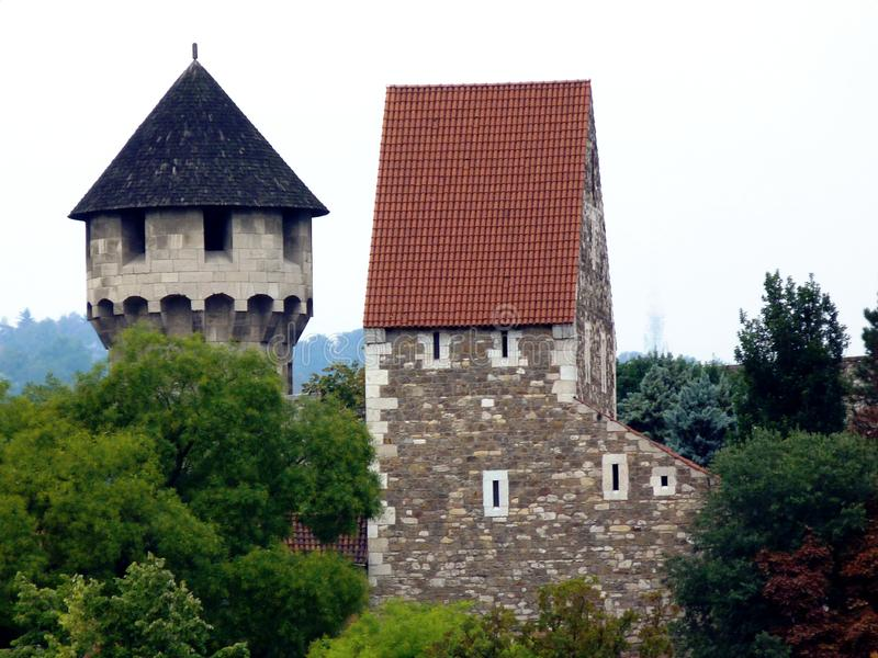 Stone tower and turret with wooden shingle of steep sloped roof and square stone fort building. Round stone tower and turret with wooden shingle of steep sloped royalty free stock photo