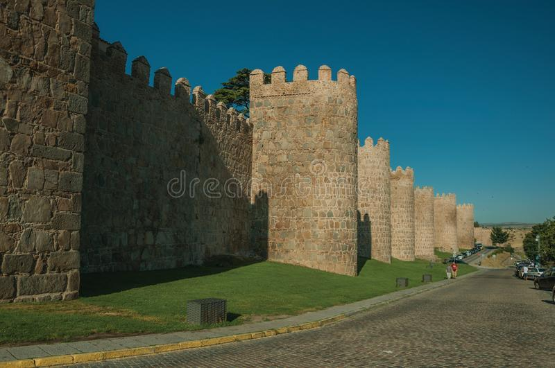 Stone towers on the large city wall next to street at Avila royalty free stock photography