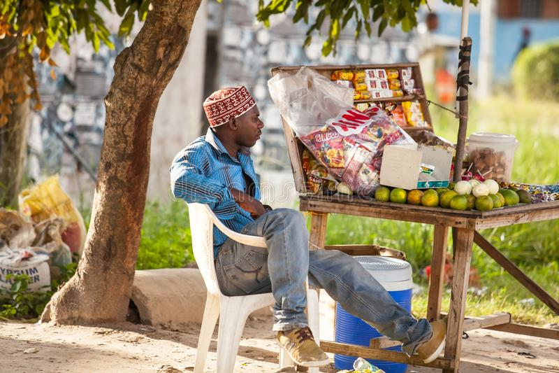 Man sitting by his food stall. stock images