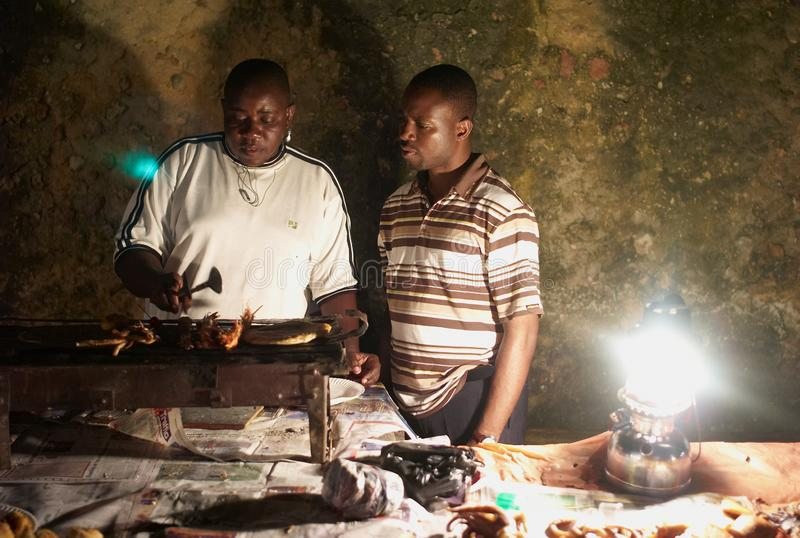 Two Men Grilling Seafood at an African Night Market. STONE TOWN, ZANZIBAR, TANZANIA - JULY 05 2008: Two men grilling seafood. Scene at a night market in Stone royalty free stock photography