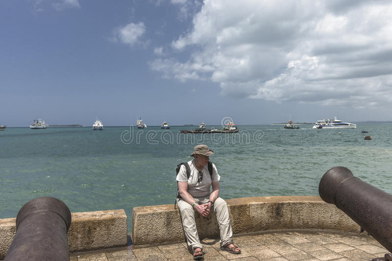 Stone Town, Zanzibar. Tourist sitting and relaxing on the seafront in Stone Town, Zanzibar, Tanzania, Africa stock photography