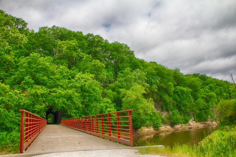 Rocheport Tunnel on the Katy Trail Along the Missouri River. The only stone tunnel on the Katy Trail, the Rocheport Tunnel pierces the tree-lined cliffs with red royalty free stock photos