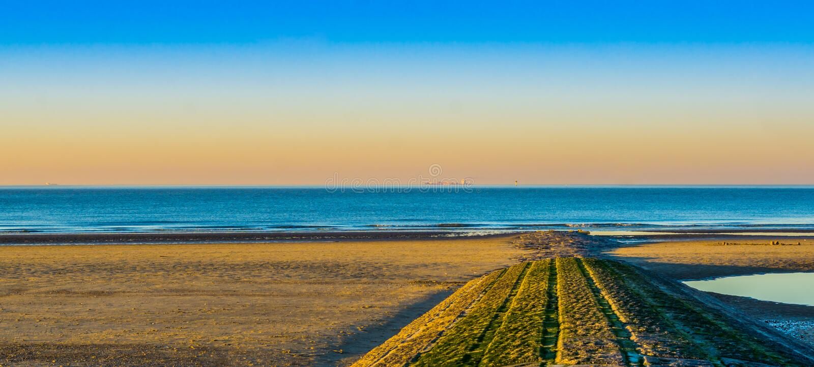 Stone walking path of rocks leading to the sea, beautiful beach at sunset in Blankenberge, Belgium stock photos
