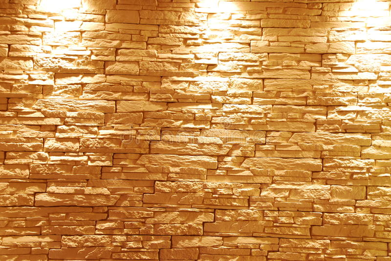 Stone wall. Gray and unshaped stone wall with lights royalty free stock photography