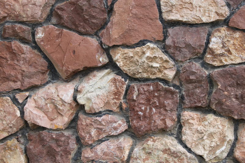 Stone wall. Stone masonry, the pattern of stone, red stone, pieces of rock, chipped stone, mosaic stone, mosaic from cleft rock, the beauty of the , iron stone royalty free stock photos