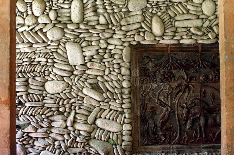 Stone Wall. An elaborate stone wall with a carved inset in Bali stock image
