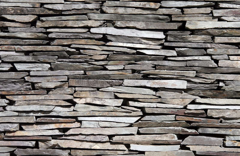 Stone Wall. Old Stone Stone Wall Made Of Many Little Pieces With Different Colours, Textured Background royalty free stock photos
