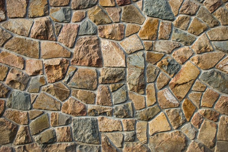 Stone wall. Built with different shapes of stones stock images