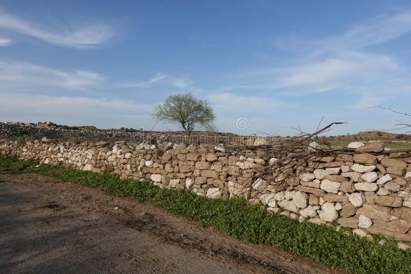 Stone wall across the road royalty free stock photo