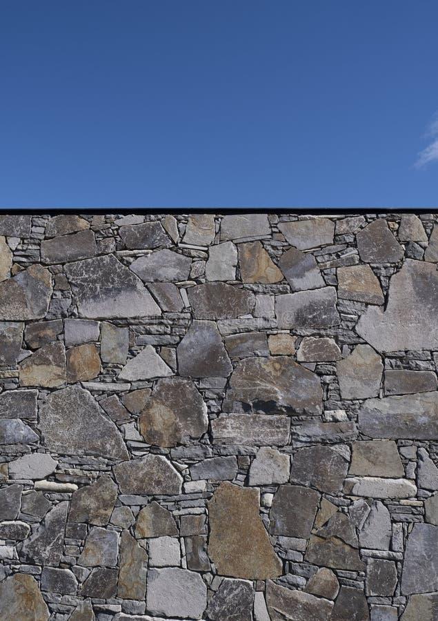 Stone wall against a sunny blue sky royalty free stock photos