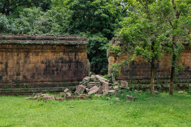 A stone wall of an ancient ruin with a big gap from a break through - angkor. The protecting stone block wall of the temple compound, which is part of the long stock photography