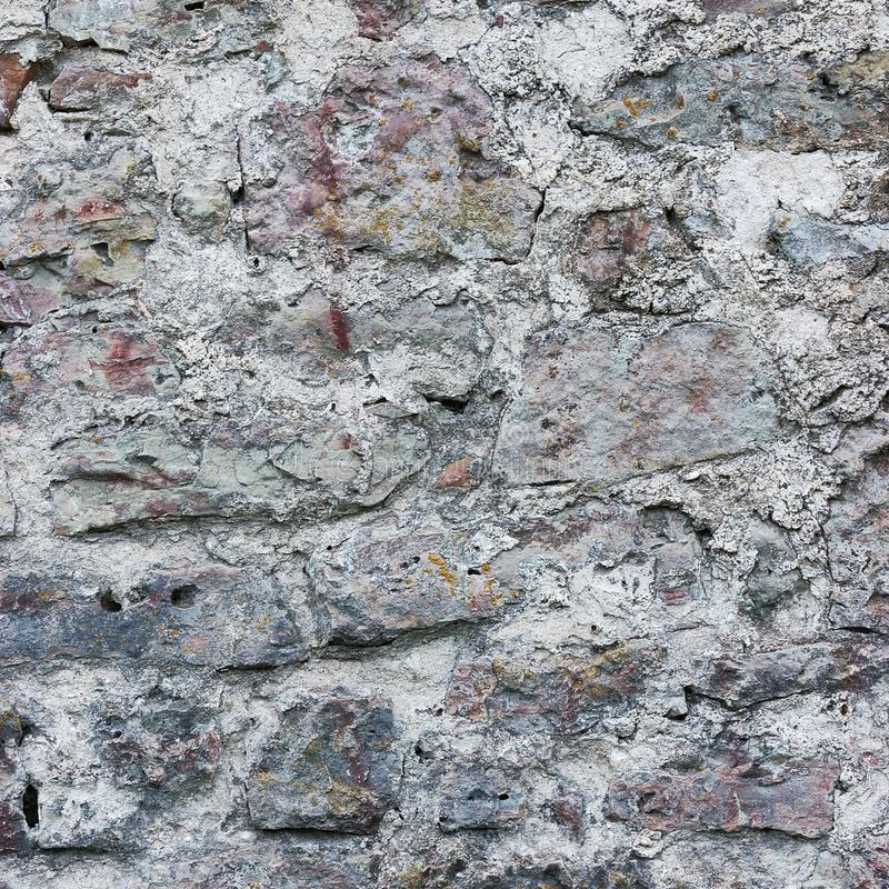 Stone wall background closeup, vertical plastered grunge red grey beige stonewall limestone pattern, old aged weathered gray lime royalty free stock photo