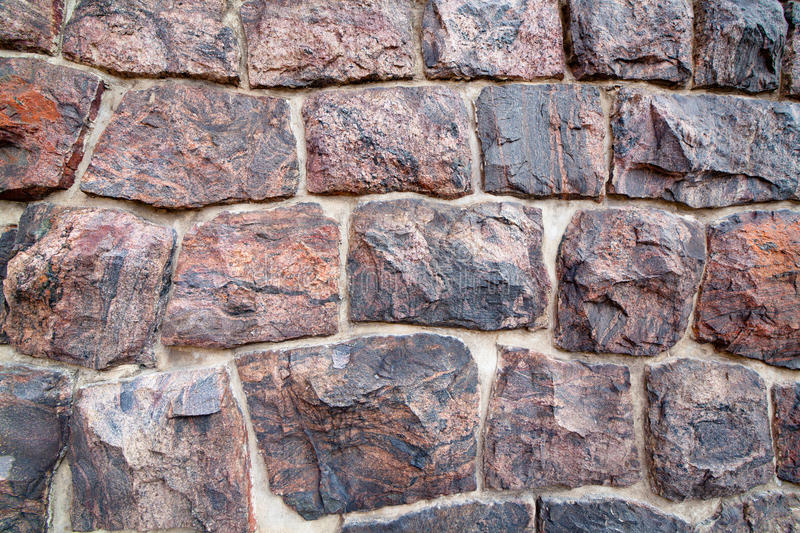 Stone wall background. The wall of the fractured granite boulders stock images