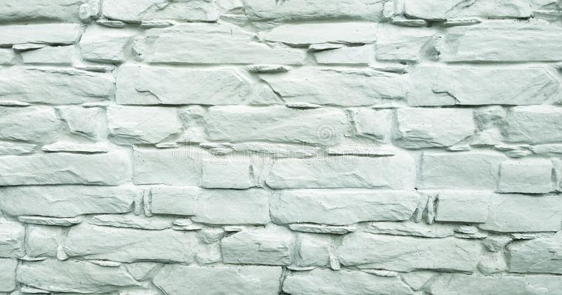 Stone wall background. White painted stone wall texture as background. Rock background wall painting. stock photo