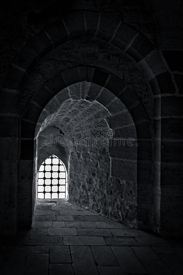 Stone wall with a backlit window with iron grid at an old citadel in Alexandria, Egypt. Stone wall with one back-lit window with iron grid at one of the passages stock photography