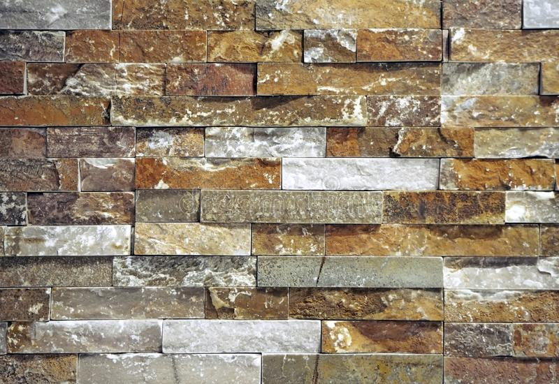 Stone wall cladding made of strips of natural rocks stacked. . Main colors are brown,red, white and gray.  stock image