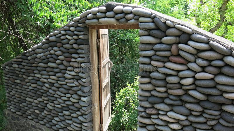 Stone wall with opened old wooden door by the road. A wall of stones in the jungle. Stones from the river that the water worked in. Stone wall with closed old stock images