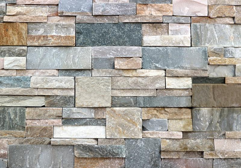 Stone wall detail with natural worked rocks of different shapes and colors. Background and texture royalty free stock photo