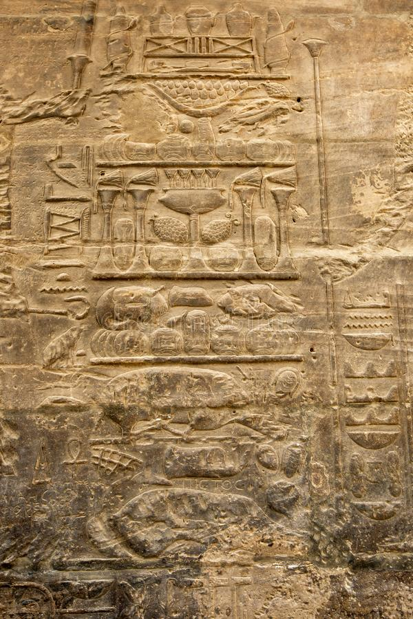 A stone wall displaying carved reliefs at Philae. royalty free stock photo