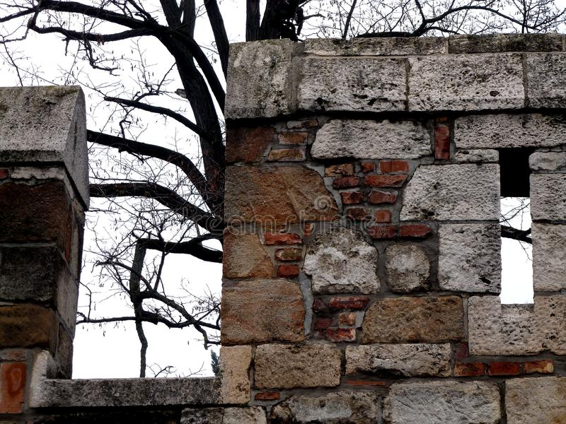 Stone Wall of Fort with Arrowslit & Patched with Brick stock photography