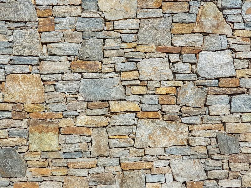 Stone Wall Full Frame Image. Stone granite wall made of stacked pieces stones. Full frame image as background stock photo
