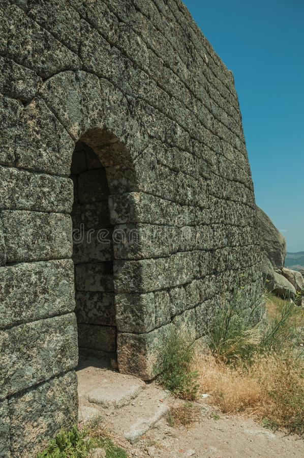Stone wall with gateway on hilltop at the Castle of Monsanto. Stone wall with gateway on hilltop covered by rocks and dry bushes, in a sunny day at the Castle of stock photography