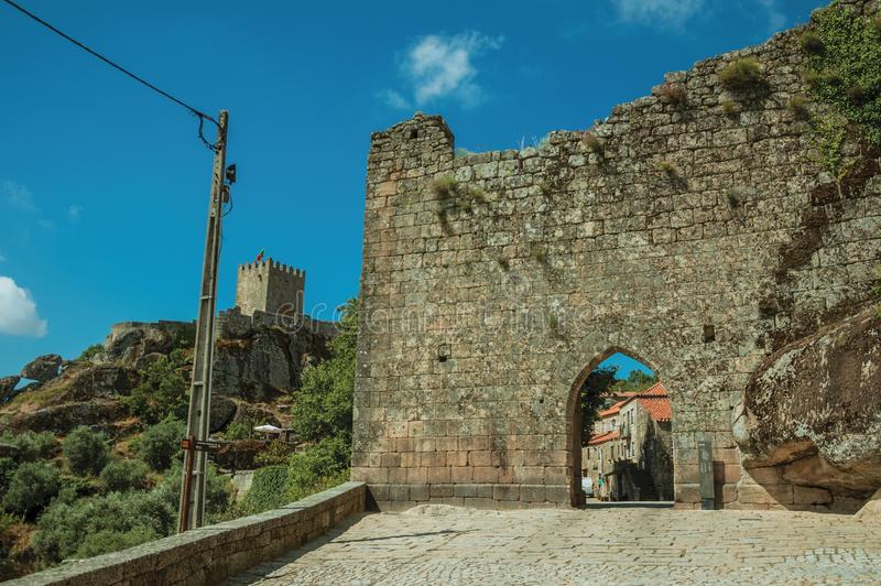 Stone wall with gateway and tower of castle over cliff. Stone outer wall with gateway and tower of Castle over rocky cliff covered by trees, in a sunny day at royalty free stock photos