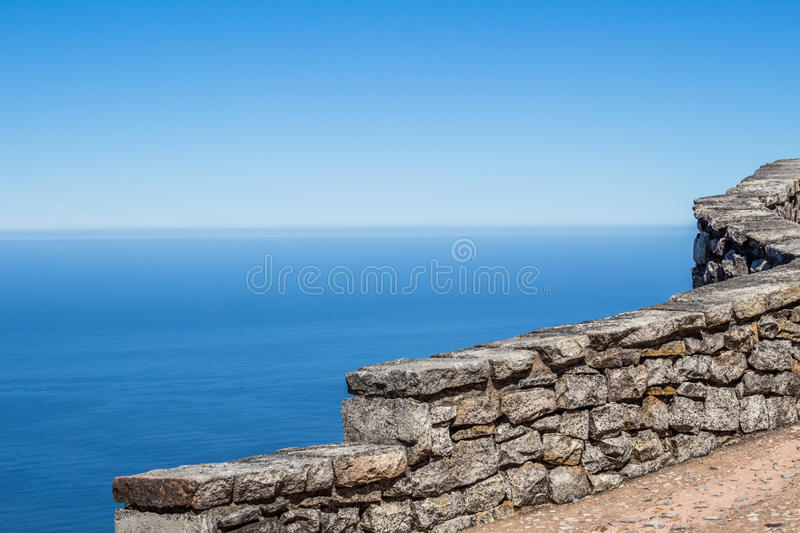 Stone wall high up on Table Mountain overlooking ocean royalty free stock image