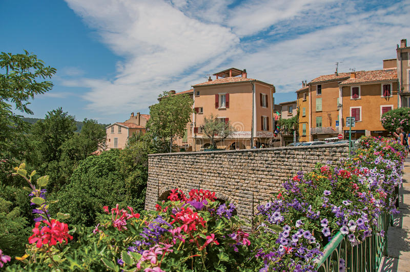 Stone wall and houses with flowers in Moustiers-Sainte-Marie. Moustiers-Sainte-Marie, France - July 08, 2016. Stone wall and houses with flowers in the lovely stock photography