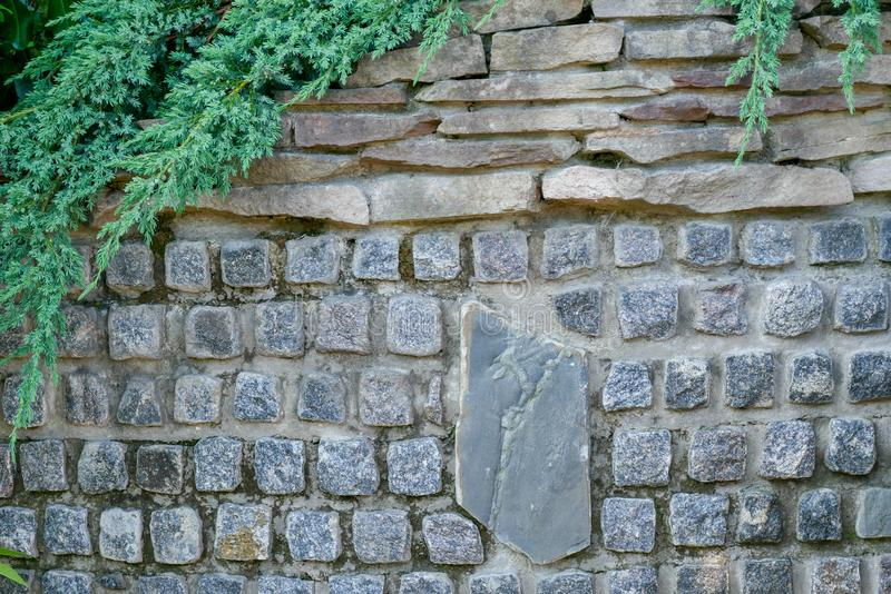 The stone wall is lined with granite stones with a large stone in the center. The stones are rough and gray in color. There are fl. At sandstone stones at the stock image