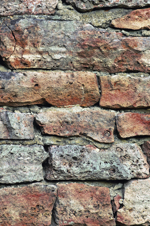 Stone wall macro closeup, stonewall pattern background, vertical, old aged weathered red and grey grunge limestone dolomite royalty free stock photos