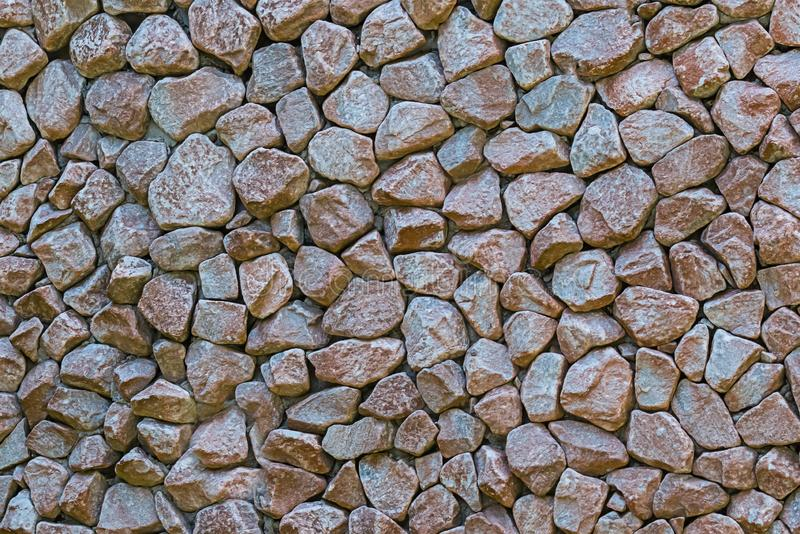 Stone wall many stone mini tiles cobblestones hard base wall background grunge style design background gray brown royalty free stock photo
