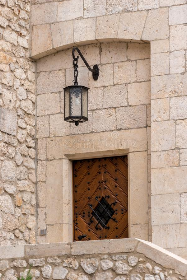 stone wall of a medieval building with a wooden door and a lantern above the entrance of a close-up stock photography