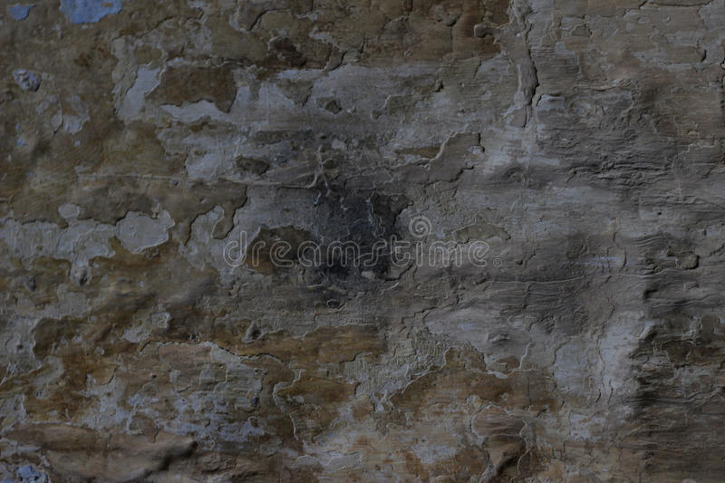 Stone wall with a multilayered old tumbling whitewash texture. Stone wall with a multilayered old tumbling whitewash Abstract background texture royalty free stock photo