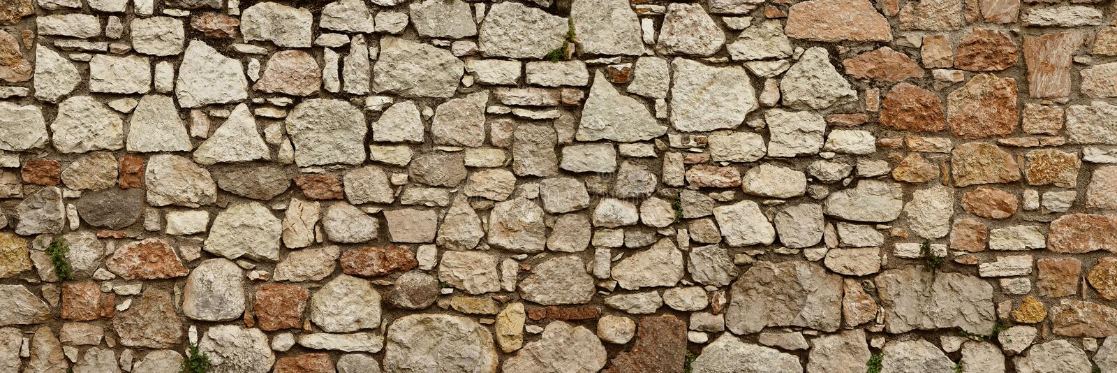 Stone wall of natural blocks in various sizes, sepia toned royalty free stock photography