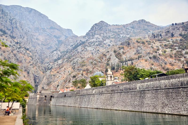 Stone wall of old fortress of Kotor, Montenegro. Church and mountains royalty free stock image
