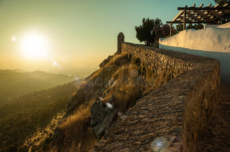 Stone wall and old house over rocky cliff in Marvao. Stone wall and old house over rocky cliff, with hilly landscape and sunset glow at Marvao. An amazing stock image