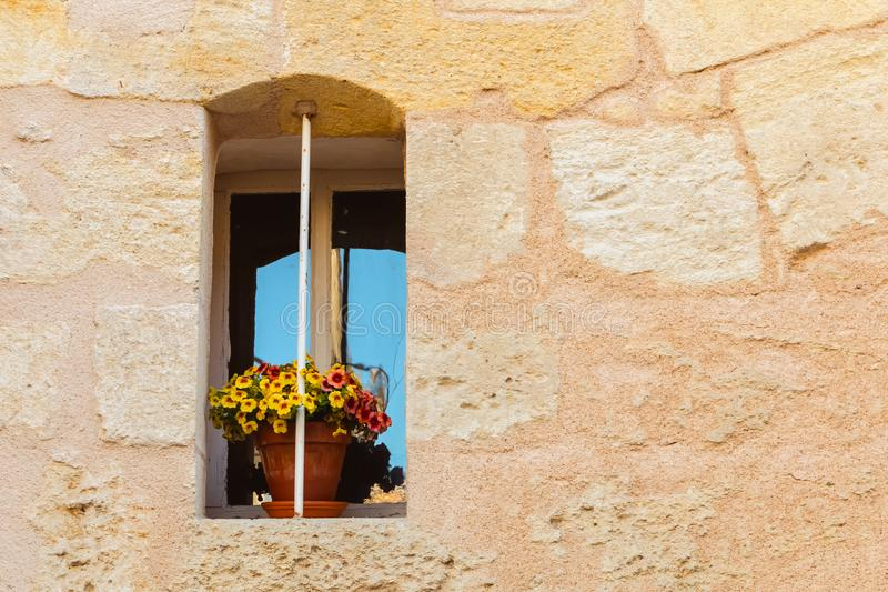 Stone wall with an old window and yellow flower pot royalty free stock photos