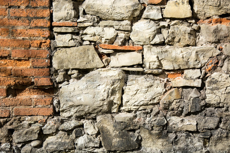 Stone wall 10. Photo of a stone wall with red bricks and sunlight royalty free stock images