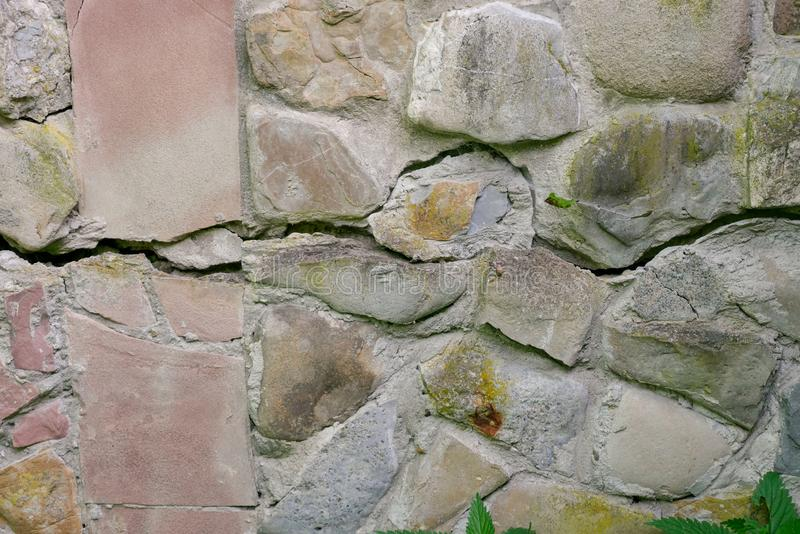 Stone wall of river stones with a large crack in the middle stock photo
