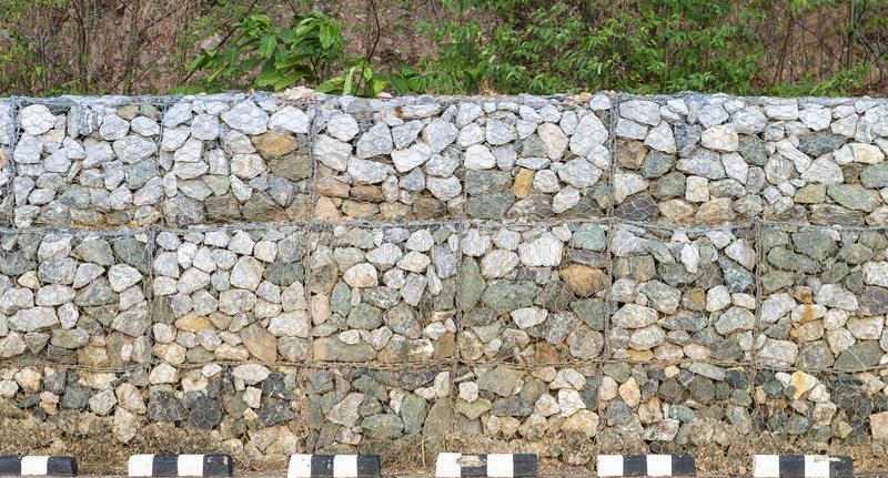 Stone wall on the road side, land slide protection stock photos