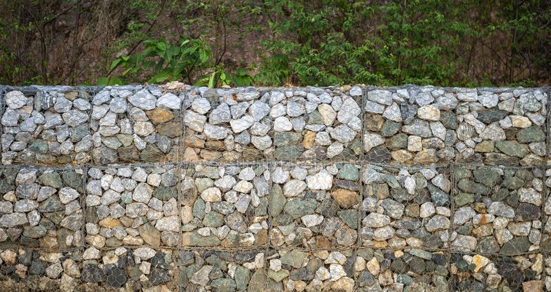 Stone wall at the road side to protect the land slide stock photography